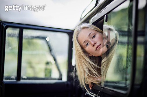 Young woman looking out of window of off-road vehicle - gettyimageskorea