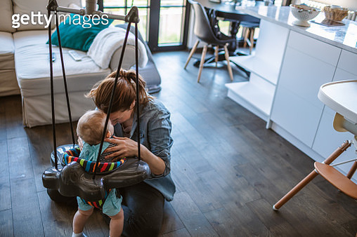 Playful mother with her baby boy at home - gettyimageskorea