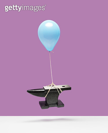 Blue helium balloon lifting heavy iron anvil off of white surface, drop shadow, purple background - gettyimageskorea