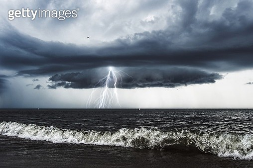 Majestic View Of Thunderstorm Lightning Over Sea Against Sky - gettyimageskorea