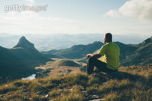 Finding the way. Man with a map sitting on a top of the mountain, looking ahead. - gettyimageskorea