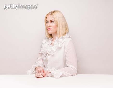 Beautiful woman sitting at white table - gettyimageskorea