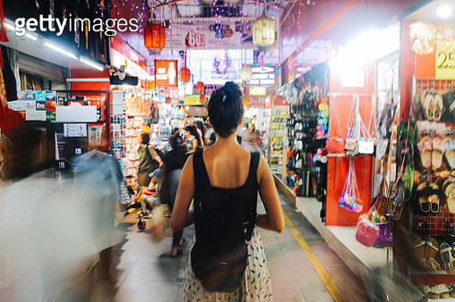 Young traveller woman walking through the small street markets in Singapore. She is carrying a backpack, strolling through the market stalls, looking for exotic and cheap stuff to buy, from technics and gadgets to delicious Asian street food. - gettyimageskorea
