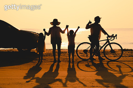 Full length of parents with children enjoying vacation on beach during sunset - gettyimageskorea