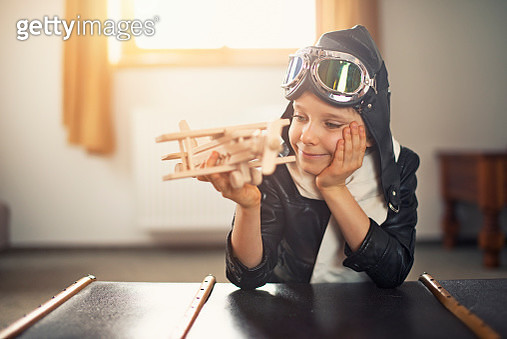 Happy little boy dreaming of becoming a pilot. The boy aged 6 is playing with toy plane - gettyimageskorea