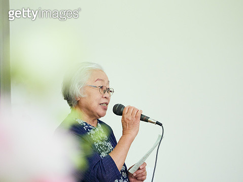 Grey-haired senior woman talking using a microphone - gettyimageskorea