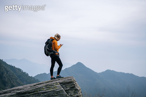 She is in an alpine meadow below a rugged rock ridge - gettyimageskorea