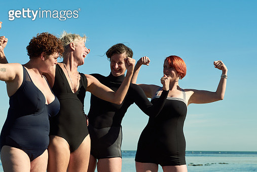 Group of women doing strong arms before a swim in the Walpole Bay Tidal Pool, Kent, United Kingdom on a bright and sunny Autumn day. - gettyimageskorea