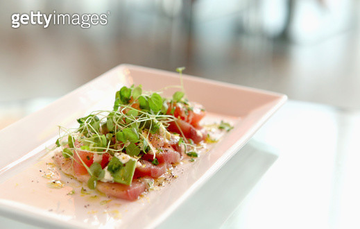 A plate of tuna sashimi with pea shoots on a table - gettyimageskorea