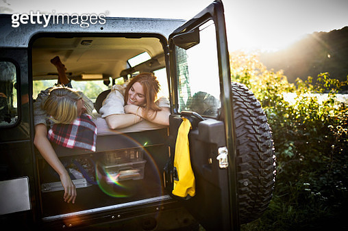 Two happy female friends lying on mattress in off-road vehicle at sunset - gettyimageskorea