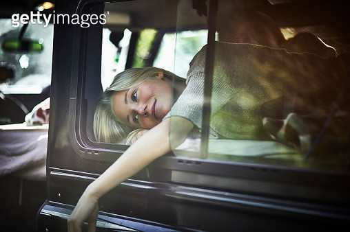 Young woman lying on mattress in off-road vehicle - gettyimageskorea