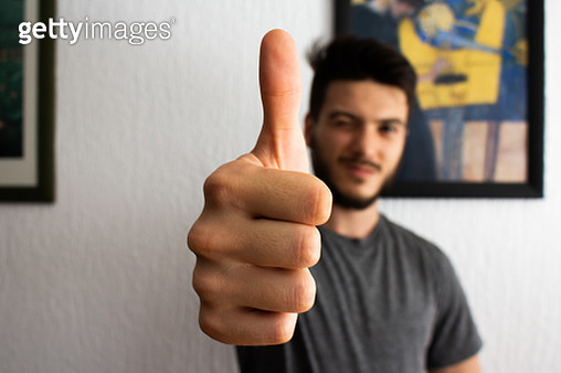 Portrait Of Man Gesturing While Sitting Against Wall - gettyimageskorea