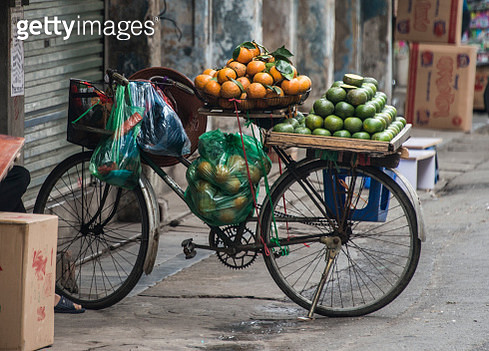 Old bicycle with oranges fruits on street market in Hanoi, Vietnam - gettyimageskorea