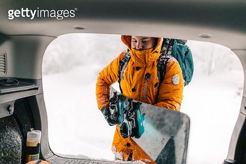Man unpacking and preparing for snowboarding - gettyimageskorea