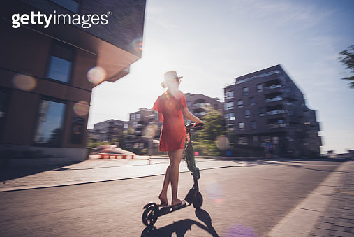 Rear view of female on electric scooter. - gettyimageskorea