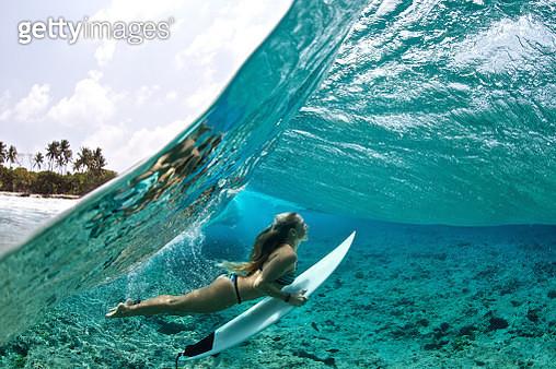 Over/under of surfer girl duck diving tropical waves - gettyimageskorea