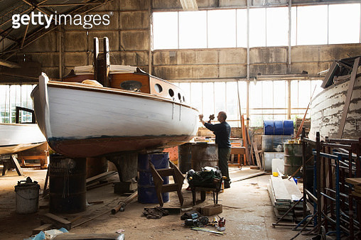 Skilled craftsman reconditioning old sailing boats in boat yard near Norfolk Broads UK. - gettyimageskorea