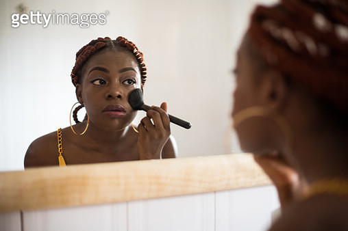 A young woman with braided hair stands by the sink in her bathroom - gettyimageskorea