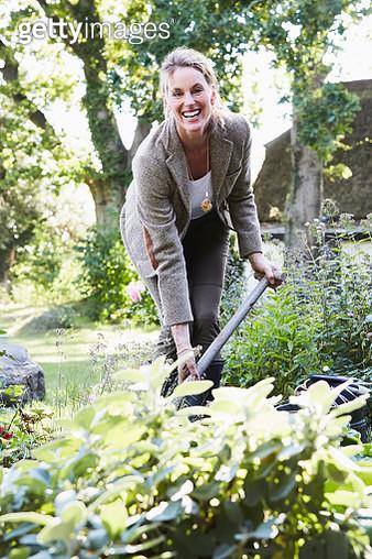 woman wearing a tweet jacket working in the garden - gettyimageskorea