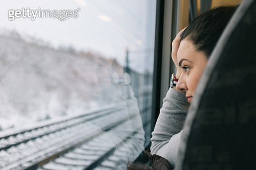 Young woman on train looking through window - gettyimageskorea