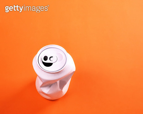 Overhead shot of a crumple aluminum can with an anthropomorphic happy face on an orange background. - gettyimageskorea