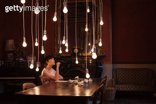 Woman sitting at table with hanging lightbulbs - gettyimageskorea