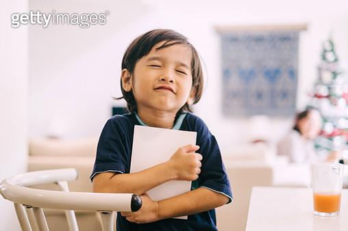 Little Cute Asian Boy Hugging a Book - gettyimageskorea