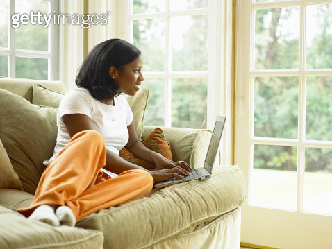 Young woman sitting on couch, working on laptop - gettyimageskorea