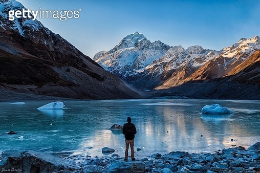 Rear View Of Man Standing By Lake Against Snowcapped Mountain - gettyimageskorea
