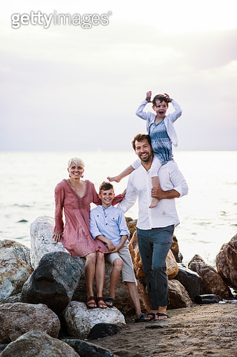 A couple with son and daughter on holiday by the sea, looking at camera. - gettyimageskorea