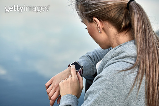 High angle view of woman using smart watch against lake - gettyimageskorea