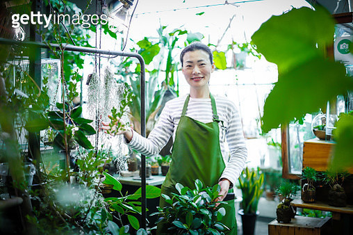 Happy young Japanese female worker working in a flower shop - gettyimageskorea