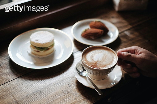 Cropped Hand Of Person Holding Coffee Cup On Table - gettyimageskorea