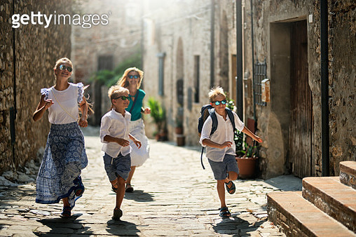 Tourist family running in beautiful Italian town. Sunny summer day in Italy, Tuscany.Family running a narrow street, talking and laughing.Nikon D850 - gettyimageskorea