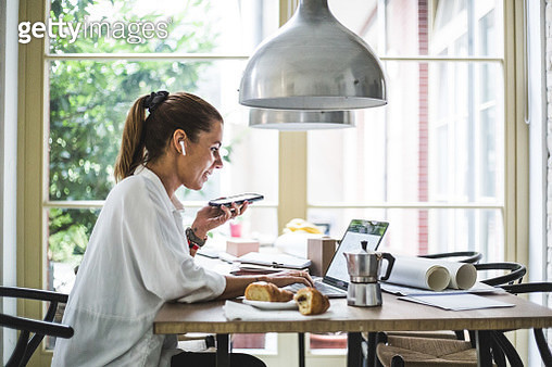 Smiling female entrepreneur using laptop while talking through smart phone at home office - gettyimageskorea