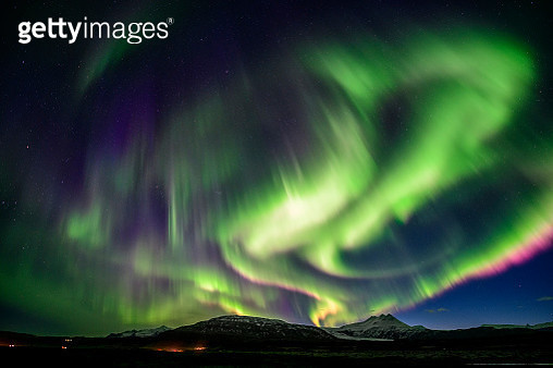 Strong Aurora over mountain at night in Iceland - gettyimageskorea