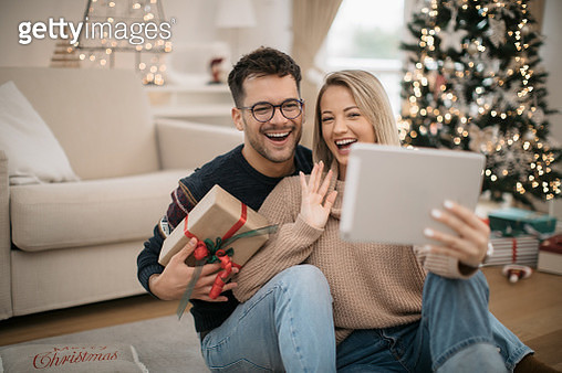 Happy Caucasian couple celebrating Christmas at home - gettyimageskorea