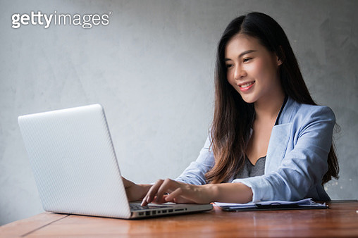 Shot of smile young businesswoman using laptop in the office. - gettyimageskorea