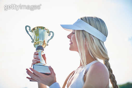 Blonde young female tennis player in visor holding championship trophy - gettyimageskorea