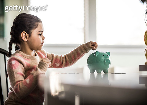 Girl (7 yrs) putting money in piggybank - gettyimageskorea