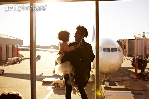 Mother holding daughter at airport - gettyimageskorea