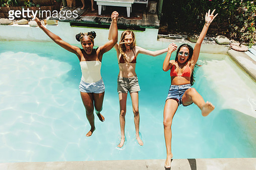 Three girlfriends falling backwards into swimming pool - gettyimageskorea