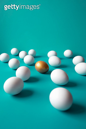 Eggs and one golden egg on the green background. - gettyimageskorea