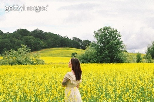 Young Woman Standing At Rape Farm Against Cloudy Sky - gettyimageskorea