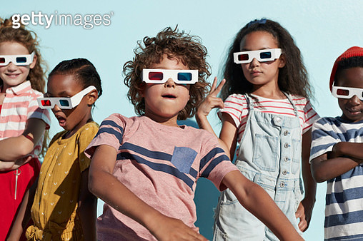 Children having joyful interaction, shot on a blue solid background on the beach in full sun - gettyimageskorea