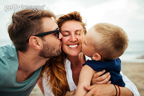 Little boy and husband kissing smiling mother on a beautiful summer day outdoors - gettyimageskorea