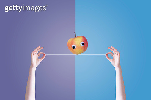Infront of a two colored background are two hands holding a wire with an apple balancing on the wire. The apple has googly eyes. - gettyimageskorea