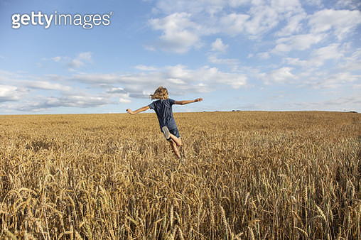 A child running under the open sky on a summer day in Denmark - gettyimageskorea