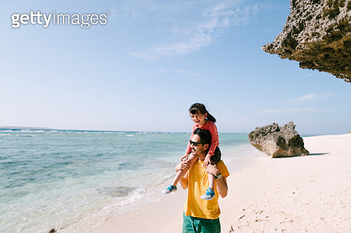 Father giving 4 year old girl piggyback ride on tropical beach, Okinawa, Japan - gettyimageskorea