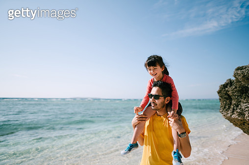 Father giving piggyback ride to his preschool daughter and walking on white sand tropical beach, Okinawa, Japan - gettyimageskorea